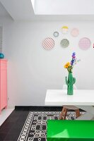 Cactus-shaped vase of flowers on white table, green bench and pastel decorative wall plates in dining room