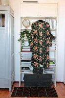 Trailing houseplant on white retro shelving, patterned dressing gown and vintage wooden trunk
