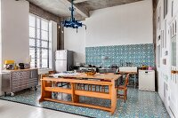 Ornate tiles and eclectic furnishings in open-plan kitchen of loft apartment