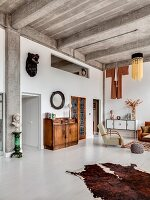 Ribbed concrete ceiling and white wooden floor in open-plan eclectic living area