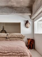 Ethnic art next to bed in bedroom with ribbon window