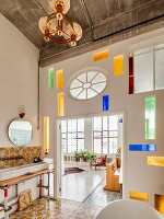 Modern stained-glass elements in partition wall between vintage-style bathroom and open-plan living area in loft apartment