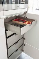An open kitchen cupboard and drawers with a view of a knife collection
