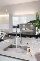 Kitchen island with an integrated sink, washing-up water and glasses