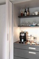 An open sliding door and a view of a kitchen cupboard with an espresso machine