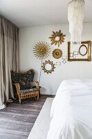 Cane chair with cushions below sunburst mirrors on bedroom wall