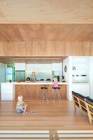 Children in open-plan interior and mother behind free-standing kitchen counter below suspended wooden ceiling,