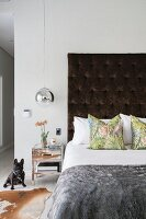 Furs and silver bedside table in contemporary bedroom