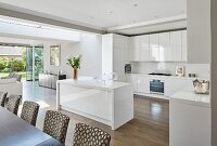 Glossy kitchen cupboards and island counter in open-plan interior