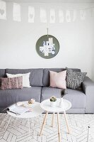 Grey sofa and white tray table in Scandinavian-style living room