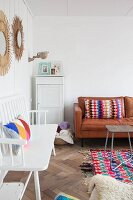 White wooden bench and colourful crocheted cushions on leather couch in living area