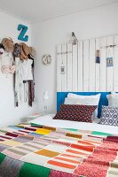 Colourful knitted patchwork blanket, headboard made from wooden boards and clothing hung from coat pegs in bedroom