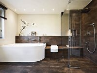 A puristic and elegant designer bathroom with a curved white bath and brown tiles