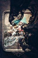 Top view of black lace cloth and various antique dolls on silver tray