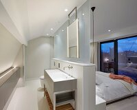 Modern bedroom with separate bathroom; washstand against free-standing partition and glass panel screening double bed