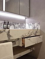 Custom marble washstand with drawer below mirrored cabinet with indirect lighting