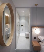 Round mirror in bedroom next to open door with view into illuminated minimalist bathroom