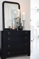 Mirror and ornaments on black chest of drawers