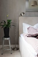 Plant on metal stool used as bedside table against grey wall