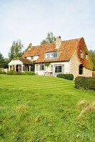 Traditional country house with renovated gable-end wall and green lawn