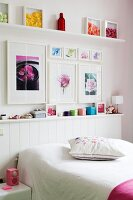 Framed floral pictures and decorated shelves in feminine bedroom