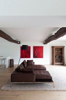 Dark brown leather couch and rustic ceiling beams in open-plan living area