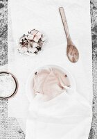 Natural fabric dye home-made from hydrangea flowers, fabric in white bowl and dying utensils