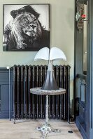 Picture of lion above ornate radiator behind table lamp on side table