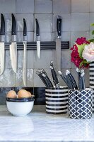 Several kitchen knives on magnetic strip in kitchen with white marble worksurface