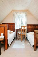 Two old wooden beds in attic room with wood-clad walls