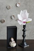 Magnolia flower in black candlestick, china figurine in black box and mother-of-pearl ornaments on wall