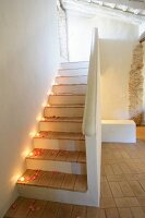 Staircase romantically decorated with tealights and rose petals in old, restored building