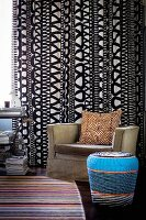 Mixture of patterns: zebra-patterned cushion on armchair in front of black and white curtain