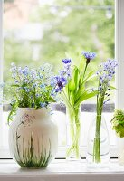 Three vases of delicate flowers on windowsill