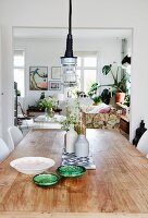 Ceramic bowls and vases of flowers on rustic table with Scandinavian-style living area in background