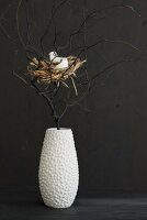 Easter arrangement of bird's nest amongst black branches in white vase against black wall