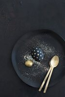 Glitter, gold spoon and gold and black Easter eggs on black plate