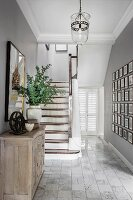 Wooden staircase, gallery of photos, cabinet and marbled tiled floor in elegant country-house hallway