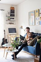 Young couple on blue sofa in retro living room