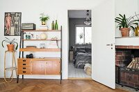 Speaker on retro shelves next to plant stand and view through open door into bedroom