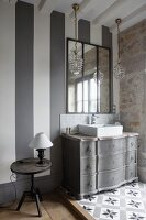 Lamp on bedside table next to sink on antique Gustavian-style chest of drawers below wall-mounted mirror