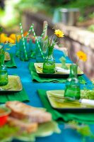 Table festively set in shades of blue and green outside
