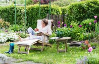 Woman on wooden lounger in idyllic allotment garden in spring