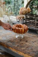 Hands of man cutting pound cake on cake stand