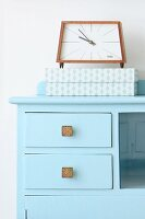 Retro alarm clock and box on top of blue cabinet
