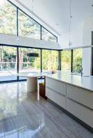 Island counter with integrated quarter-round bench at one end opposite glass wall with view of garden