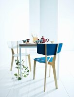 Pair of chairs at square table set with tea service and tendril of ivy