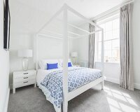 A bedroom with a white four poster bed and a grey carpet
