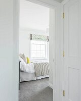 A view of a bright guest room with a lattice window and a grey carpet in an old building