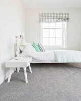 A white bed and a bedside table on a grey carpet